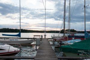 Am Tegler See sieht man einen Steg mit einigen Segelbooten die im Hafen festgemacht sind